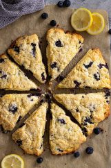 Top down view of lemon blueberry scones with slices of lemons for garnish.