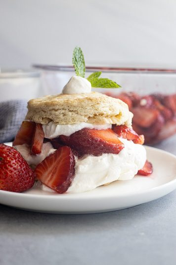 Strawberry Shortcake on a white plate. Juicy strawberries and freshly whipped cream.