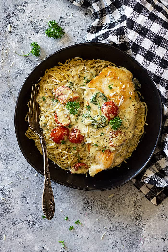 Bowl filled with pasta and topped with creamy tuscan chicken.