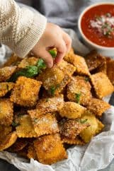 Toasted ravioli sprinkled with parmesan cheese and chopped basil. A child's hand is taking one to eat.