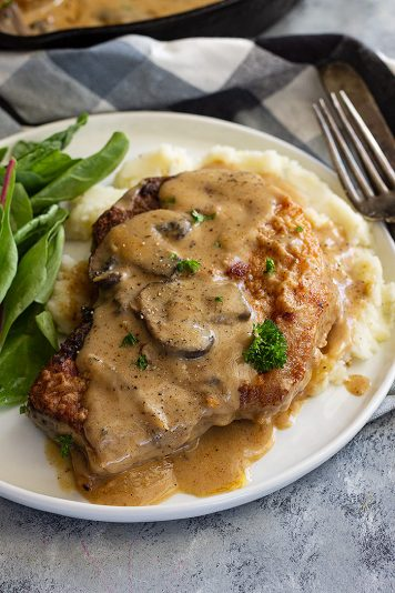 A pork chop on a plate with mash potatoes and topped with a creamy mushroom gravy.