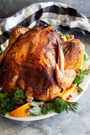 Beer and Butter Turkey on a platter decorated with fresh herbs, sliced oranges, and pomegranate seeds.
