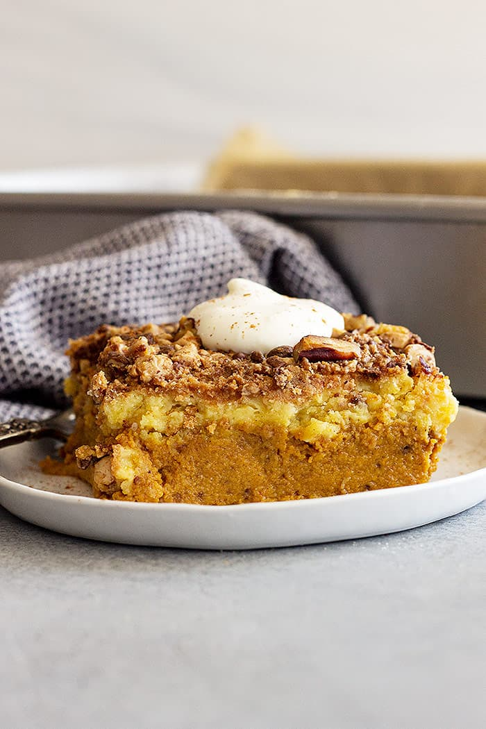 Large piece of pumpkin dump cake on a white plate topped with freshly whipped cream.