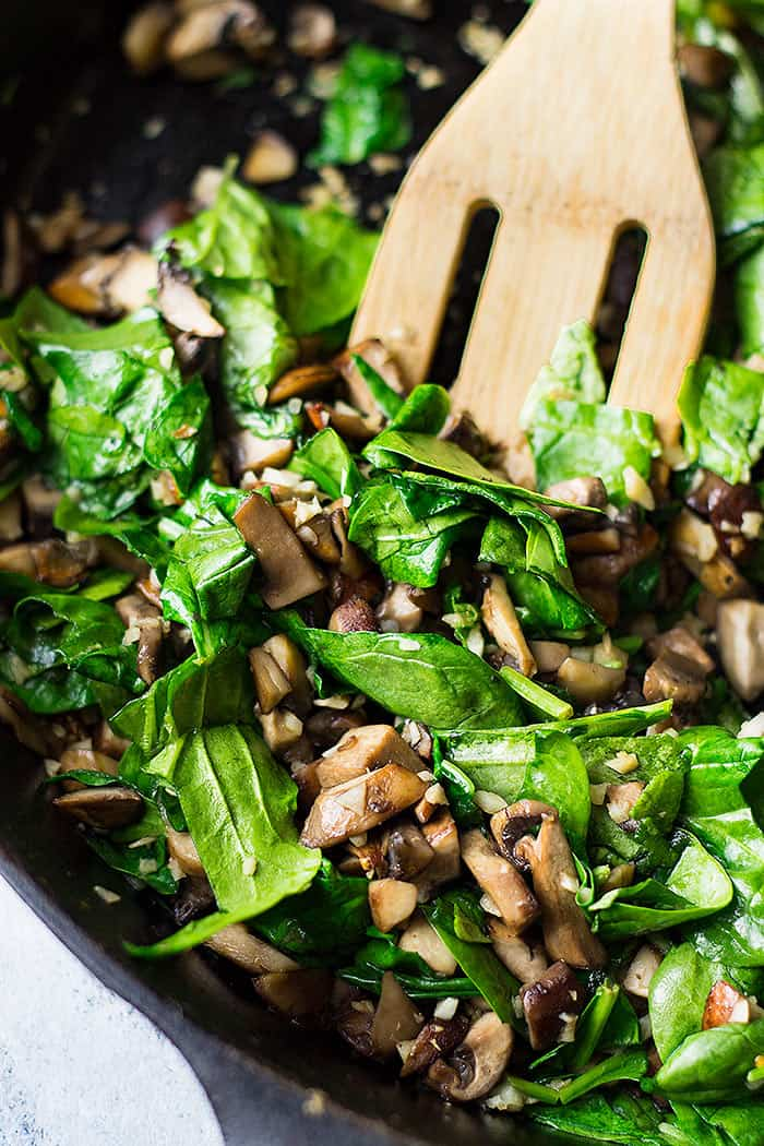 Chopped mushrooms and spinach in a skillet cooking.