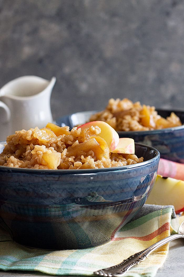 Two bowls of Slow Cooker Cinnamon Apple Breakfast Rice garnished with fresh apples.
