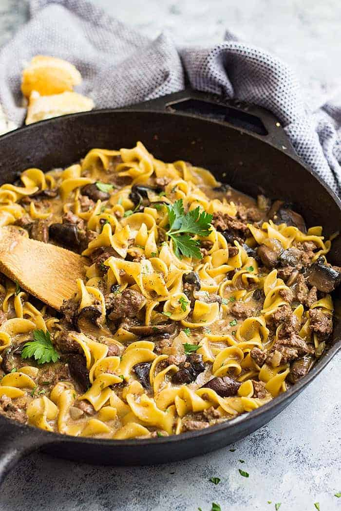 One pot hamburger stroganoff in a pan with a wooden spoon in it.