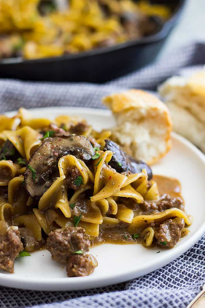 One pot hamburger stroganoff on a plate with a piece of bread to the side.