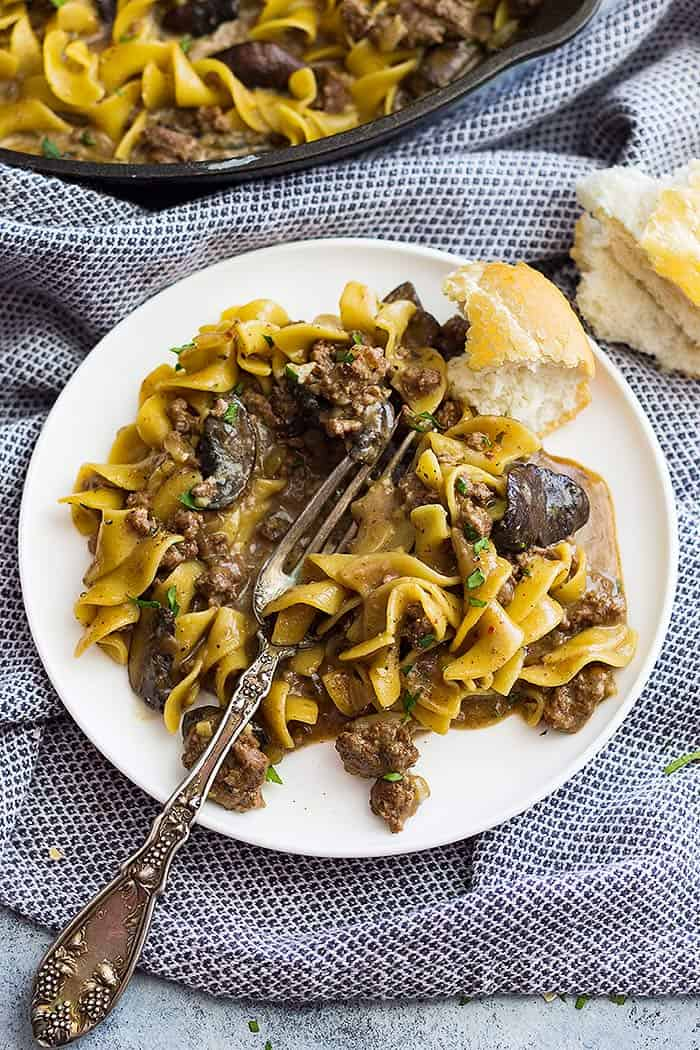 A top down view of one pot hamburger stroganoff on a plate with a piece of bread to the side.