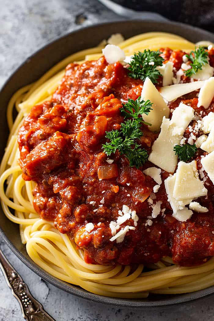 A large plate of spaghetti piled high with sauce and cheese.