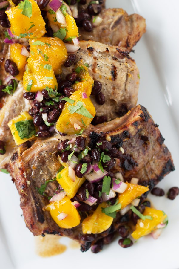 Citrus Marinated Pork Chops with Mango Black Bean Salsa -a juicy marinated pork chop grilled to perfection. Topped with a sweet and savory mango salsa! | www.countrysidecravings.com