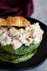 Apple tuna salad piled on a buttery croissant with a leaf of lettuce..