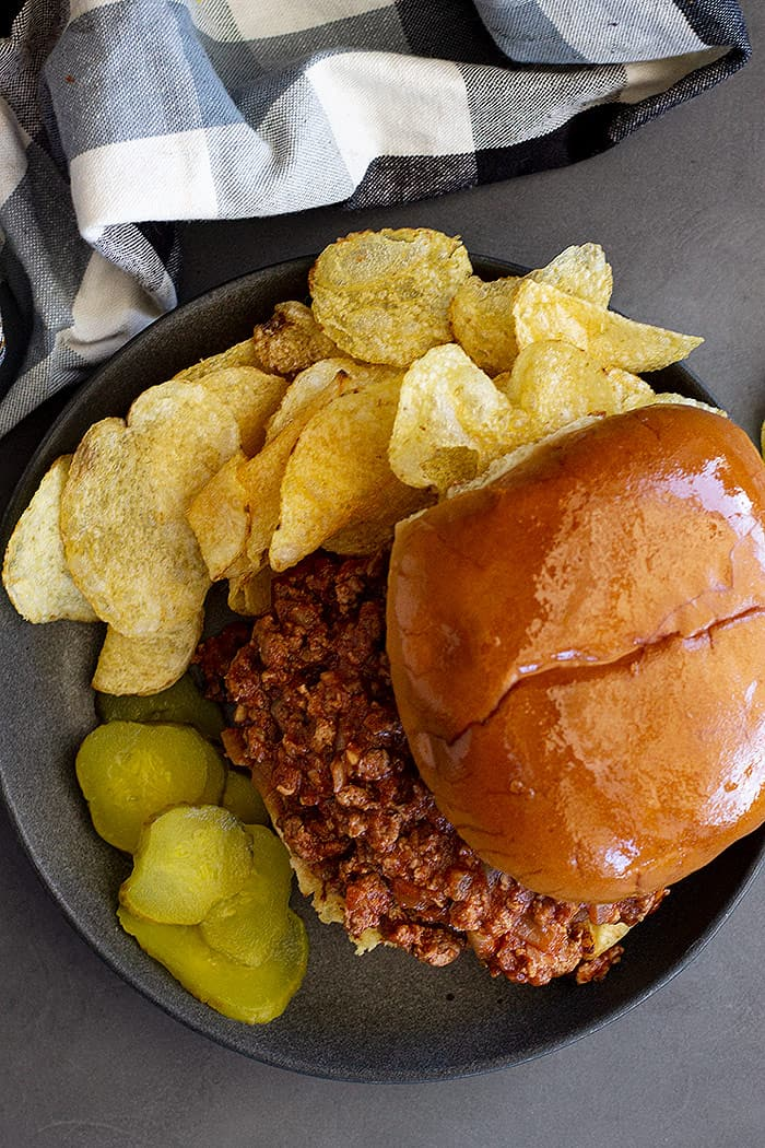 Top down of a sloppy joe on a plate with chips and pickles.