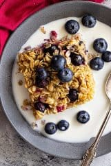 Baked oatmeal in a bowl topped with fresh blueberries and a splash of milk.
