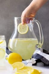 Dropping a cut lemon into the lemonade.