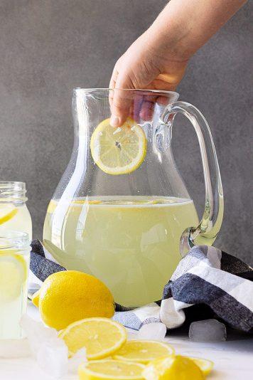 Dropping a cut lemon into the lemonade.