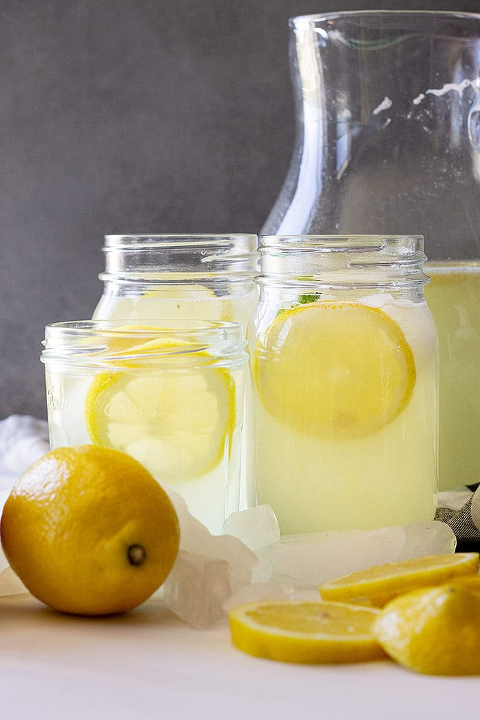 Glasses of lemonade with lemons as garnish.