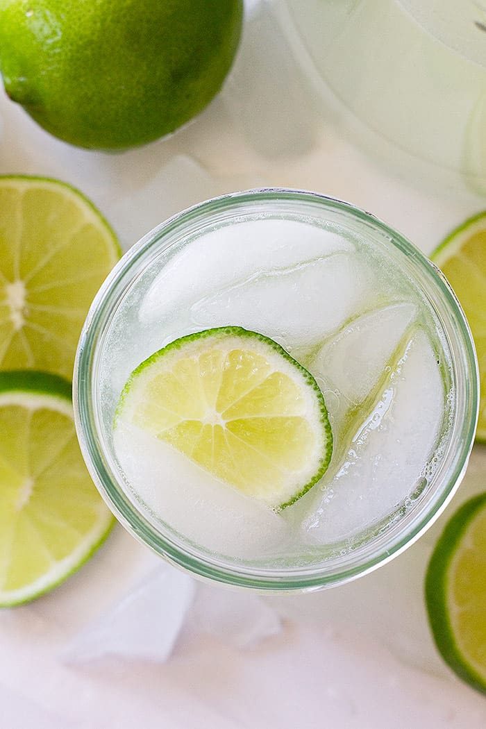 Top down view of limeade in a glass with a slice of lime and ice.