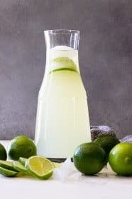 A tall pitcher of limeade with fresh limes as garnish.