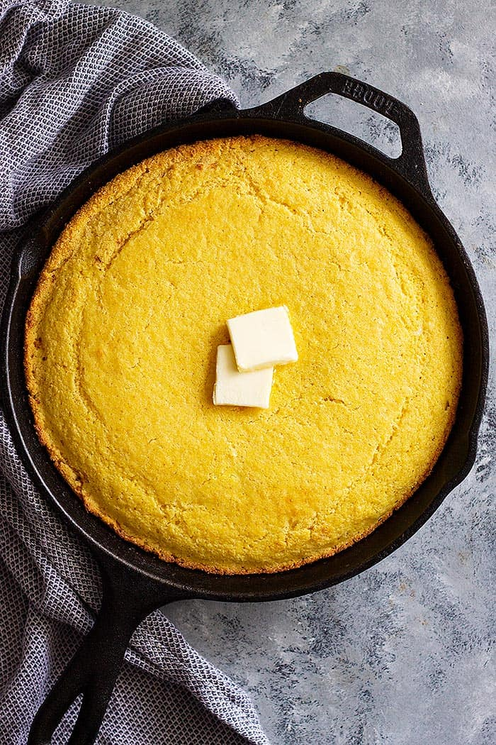 This easy Buttermilk Cornbread recipe is the only one you'll ever need! It can be sweet or savory, has a tender moist crumb, and it's made in one bowl! This Buttermilk Cornbread is a quick and easy recipe that makes the best cornbread! It has a nice tender crumb that's perfectly moist. And you can make it in a cast iron skillet or baking dish! This Buttermilk Cornbread recipe is the best cornbread ever!! Choose to make it sweet or savory by adjusting the sugar. It has a tender moist crumb and is perfect drizzled with honey! #cornbread #easyrecipe #sweetcornbread