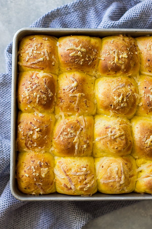 Pan of golden savory pumpkin rolls topped with parmesan cheese.