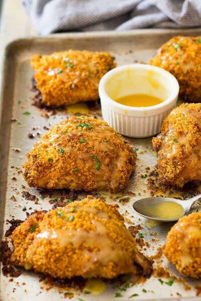 Crispy baked chicken thighs on a sheet pan with a honey mustard sauce beside.