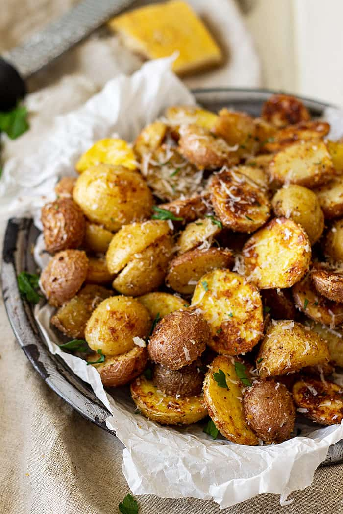 A bowl of roasted potatoes on a table ready to be served.