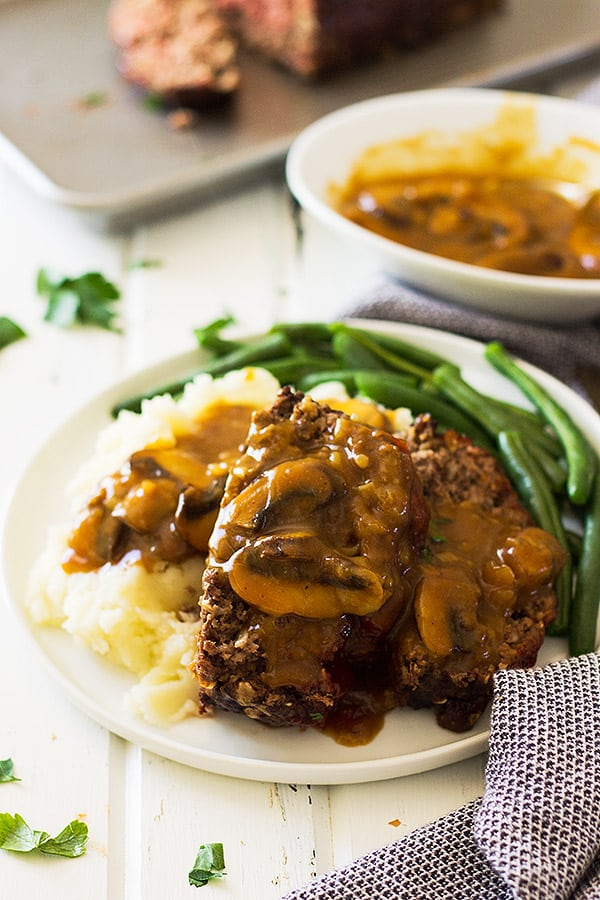 Old Fashioned Meatloaf sliced on plate with gravy, green beans, and mashed potatoes.