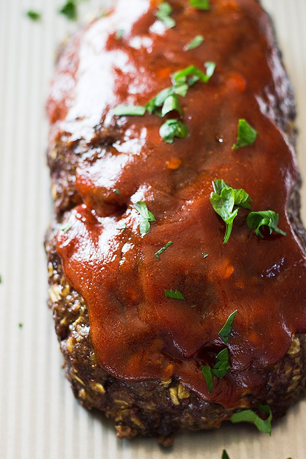 Whole Old Fashioned Meat Loaf with saucy topping and fresh parsley