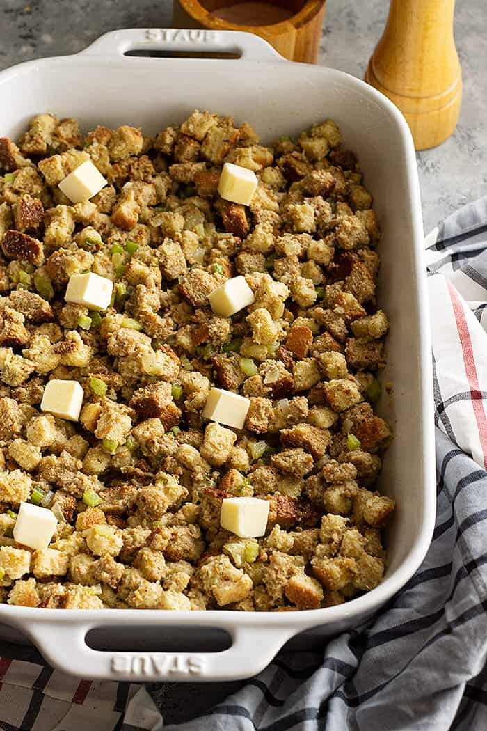 Classic stuffing in a baking dish dotted with butter ready to be baked