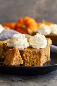 Close up of a slice of traditional pumpkin pie with a bite taken out to show how smooth and creamy it is.