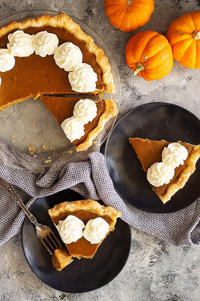 Top down view of pumpkin pie slices decorated with whipped cream.