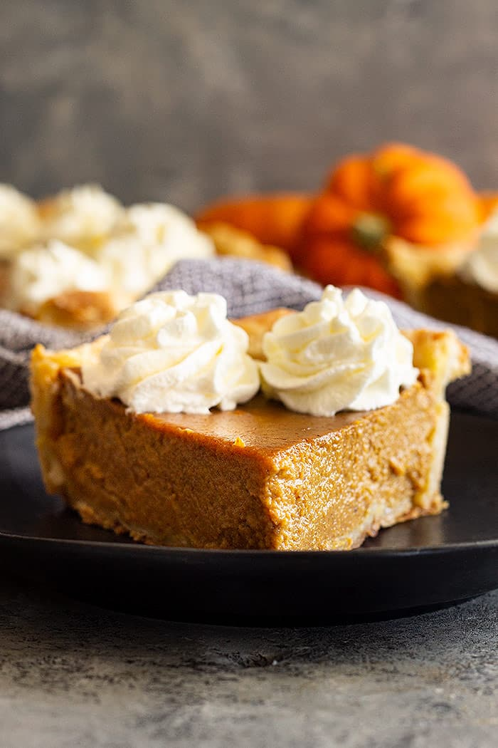 Close up of a slice of pumpkin pie with whipped cream on top.