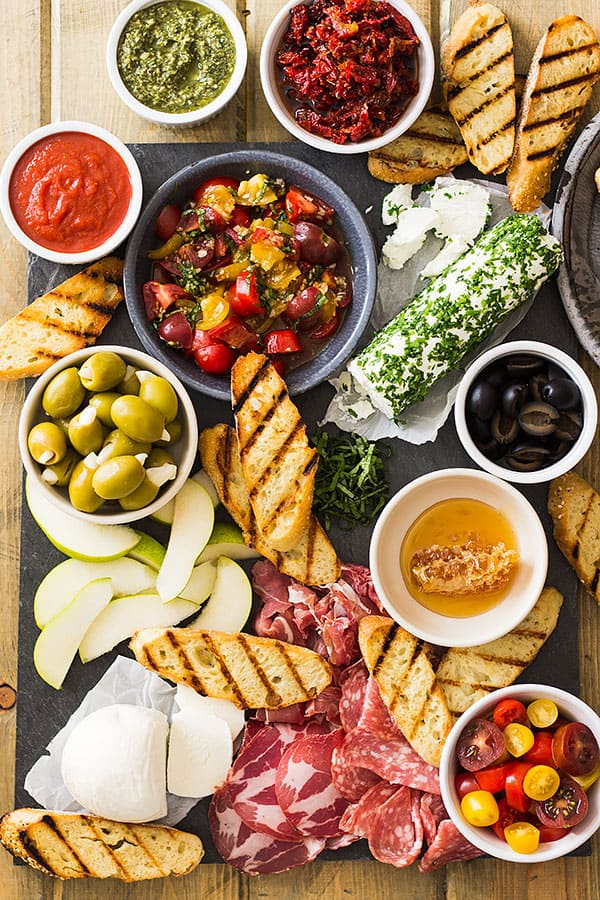 Full overhead view of bruschetta bar with grilled bread, toppings, cold cuts, and cheese.