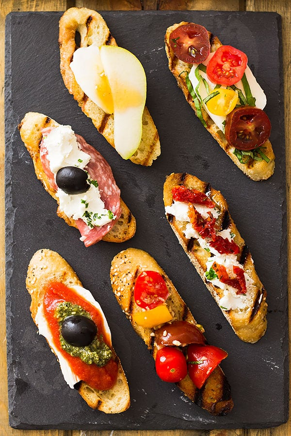 Slices of grilled bread bruschetta on a slate board with different toppings.