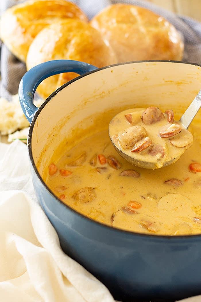 Big pot of Creamy Cajun Potato Soup with a ladle ready to dish up soup.