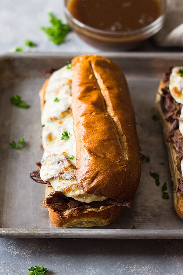 A french dip sandwich with melted cheese on a baking sheet.
