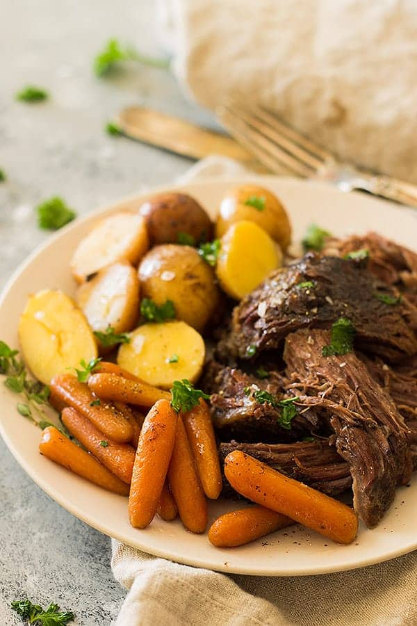 Crazy tender, melt in your mouth slow cooker pot roast with carrots and potatoes. This super easy meal requires little prep and the crockpot does all the work! | www.countrysidecravings.com
