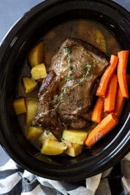 pot roast in slow cooker with carrots and potatoes.
