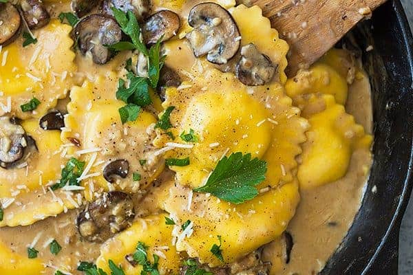 This Cheese Ravioli in Creamy Mushroom Sauce is made easy using store bought ravioli and made extra decadent with a simple garlic mushroom cream sauce! | www.countrysidecravings.com