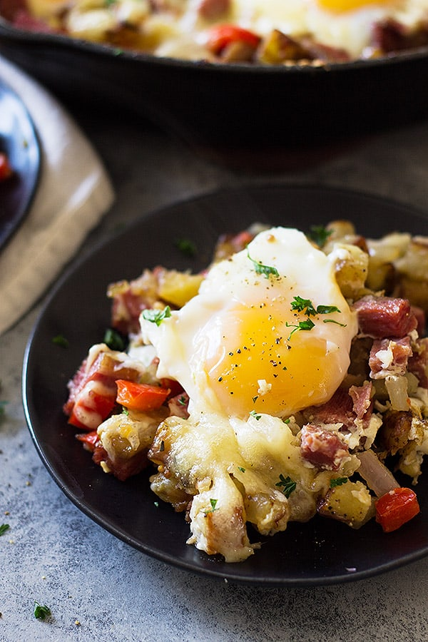 This Cheesy Corned Beef Hash with Baked Eggs is an easy one pan breakfast recipe! Filled with meat, potatoes and eggs makes for a hearty and satisfying breakfast! | www.countrysidecravings.com
