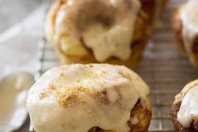 These Cinnamon Roll Muffins are a tender homemade yeast roll made in a muffin tin! Topped with a delicious vanilla icing makes these the perfect breakfast! | www.countrysidecravings.com