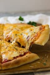 This Homemade Three Cheese Pizza using homemade pizza dough and sauce. It's topped with gooey mozzarella, cheddar and Parmesan cheese then baked to perfection!   www.countrysidecravings.com