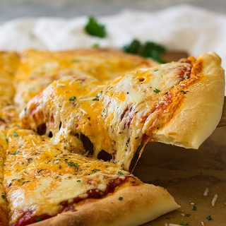 This Homemade Three Cheese Pizza using homemade pizza dough and sauce. It's topped with gooey mozzarella, cheddar and Parmesan cheese then baked to perfection! | www.countrysidecravings.com