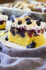 One piece of lemon blueberry poke cake on white plate with blueberries
