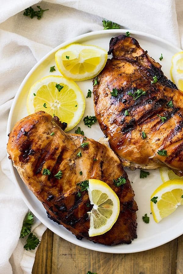 Two chicken breasts on white plate with lemon wedges after marinating in simple marinade for chicken