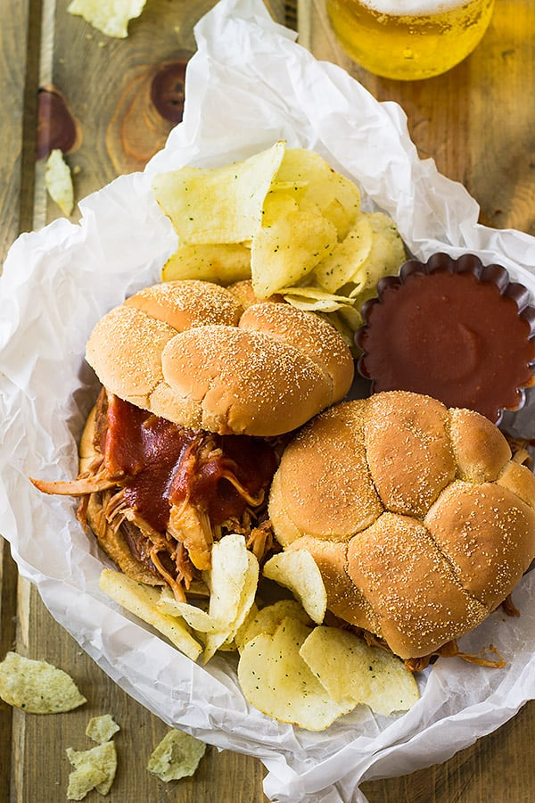 two pulled pork BBQ sandwiches with chips in white paper basket