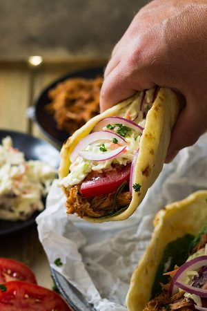 These BBQ Pulled Pork Gyros feature a nicely seasoned slow cooker pulled pork, homemade creamy coleslaw, and a sweet and sticky bbq sauce.