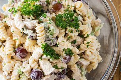 top shot of pasta salad with red grapes in clear glass mixing bowl