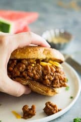 hand holding slow cooker beef and bean sloppy joes above white plate
