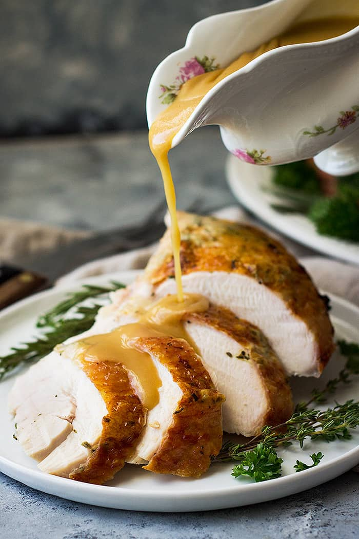 Pouring gravy over turkey breast sliced on white plate with fresh herbs.